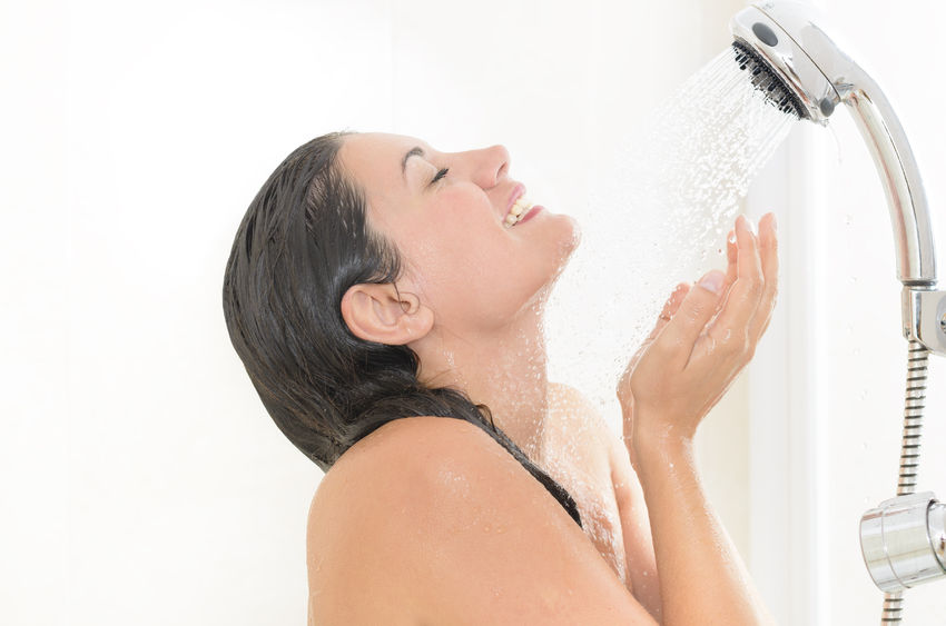 42034203 - woman taking a shower enjoying water splashing on her